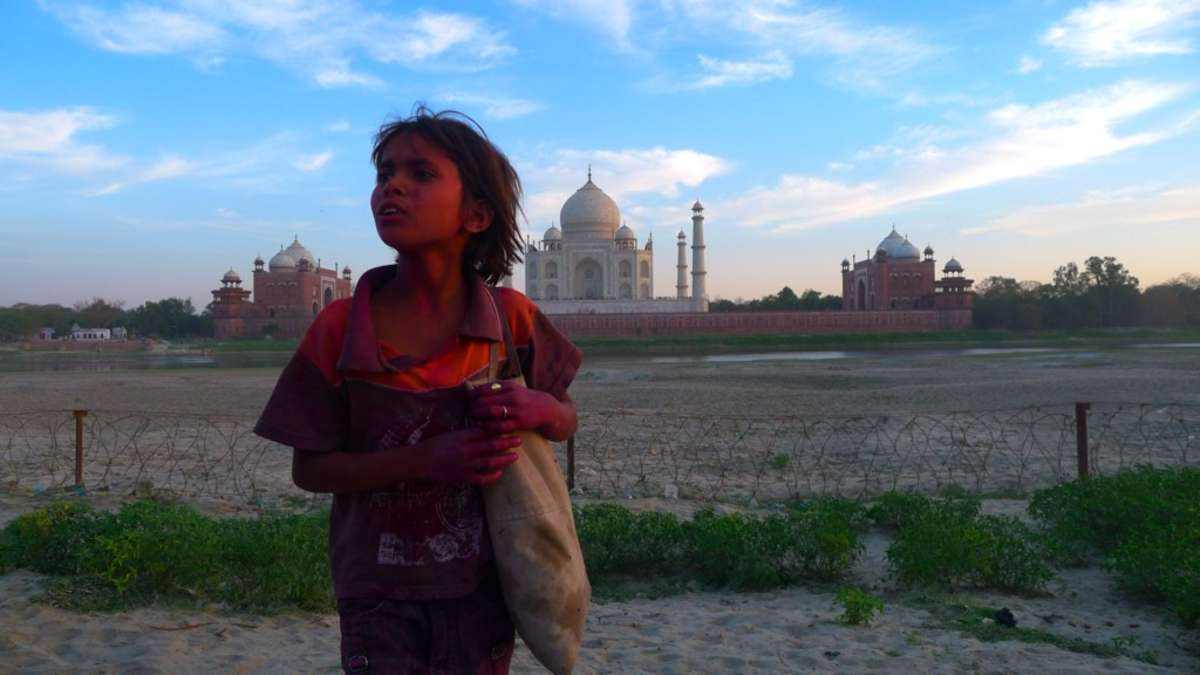 Child covered in pink paint with Taj Mahal behind in the distance