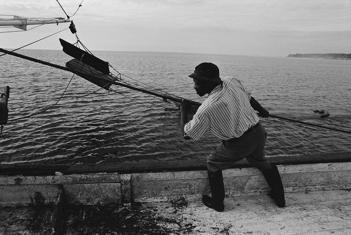 black and white image of man pulling in line on a boat