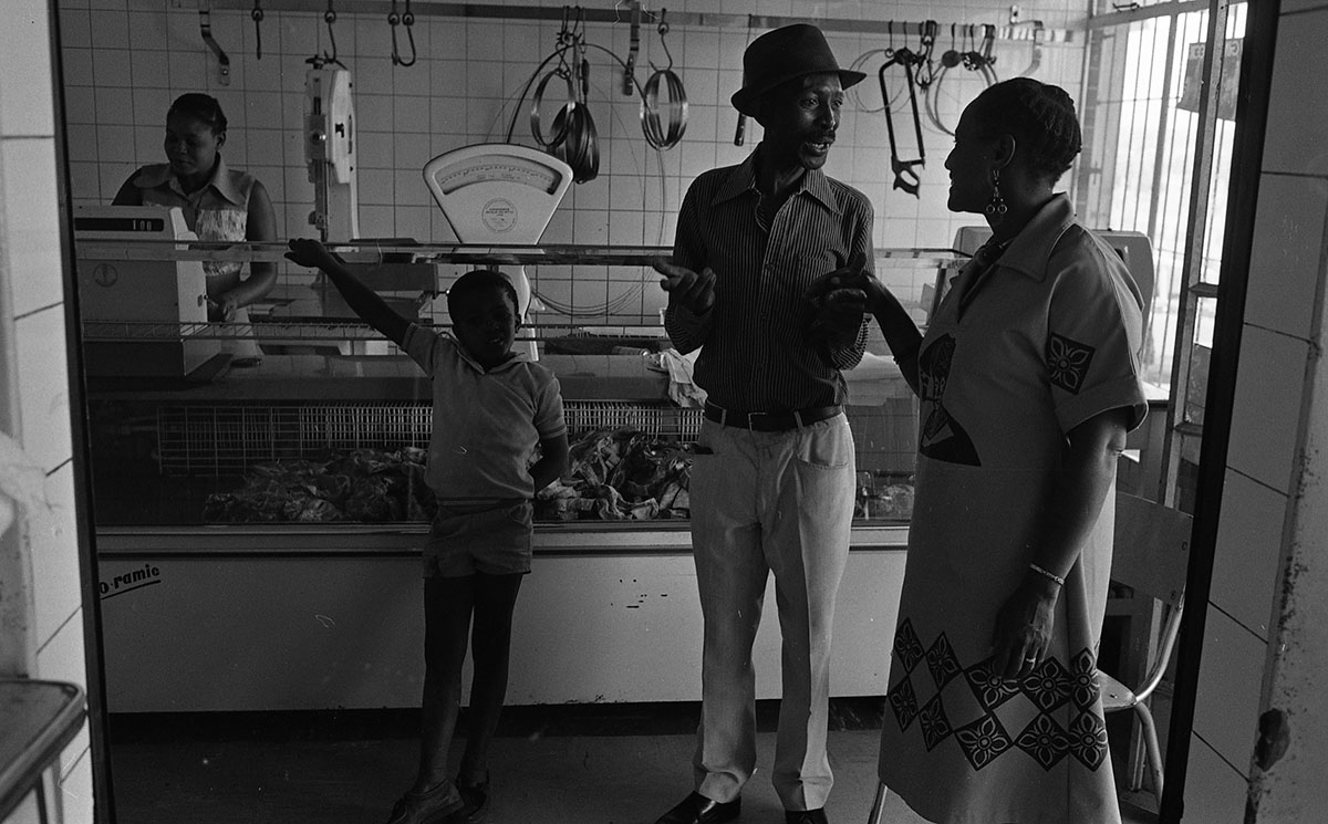 Black and white image of people at counter in shop