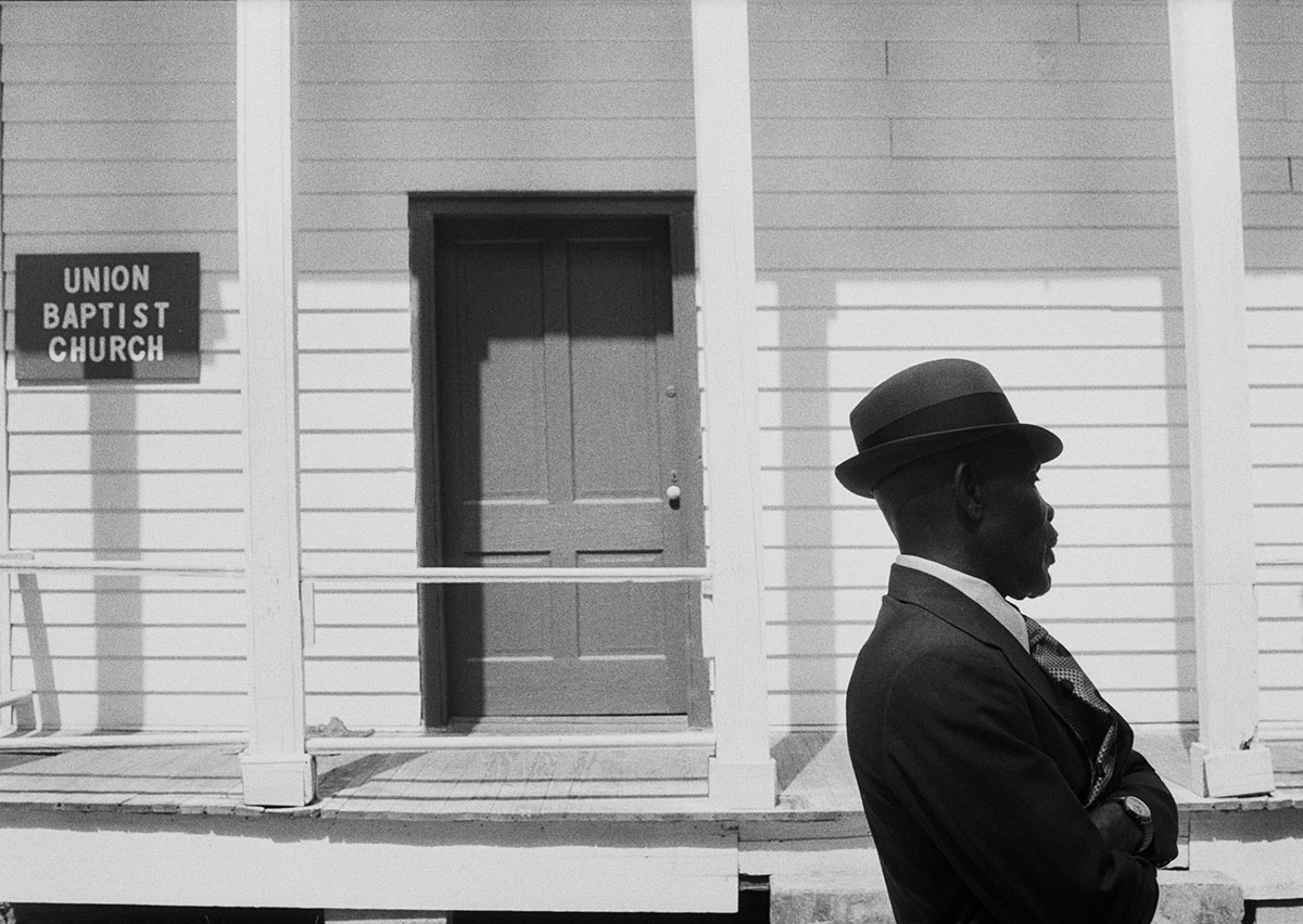 photograph of man in suit and hat walking past front of white church